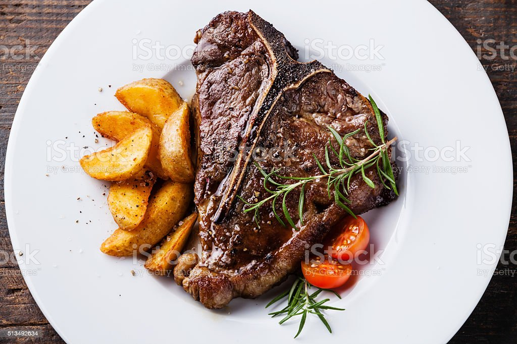 Grilled T-Bone Steak with roasted potato wedges stock photo