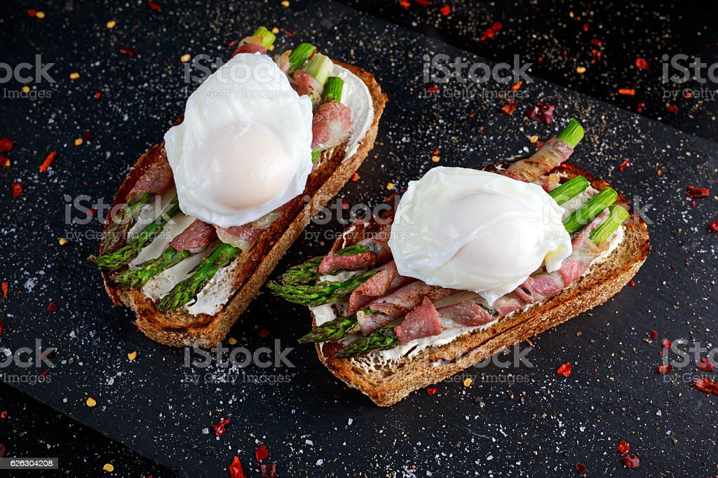 Grilled Toast witch Asparagus, Poached egg, bacon on stone background stock photo