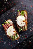 Grilled Toast witch Asparagus, Poached egg, bacon on stone background