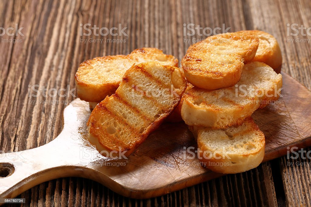 Grilled toasts on old wooden background stock photo
