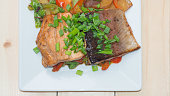Grilled trout on white square plate