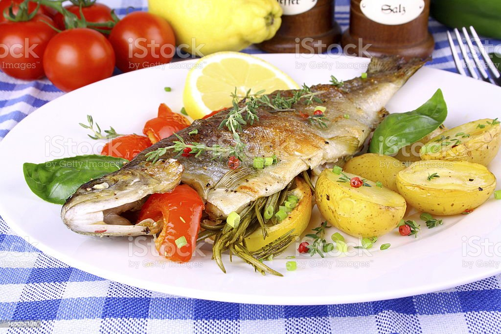 Grilled trout with potato, red pepper and lemon royalty-free stock photo