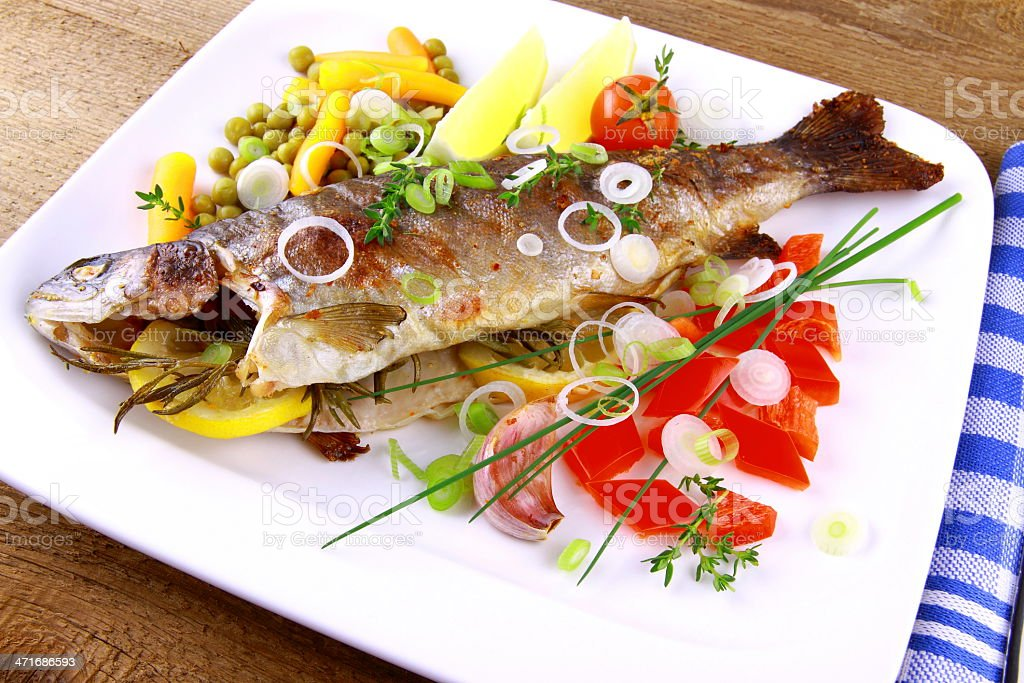 Grilled trout with quite fine vegetables on wood background royalty-free stock photo