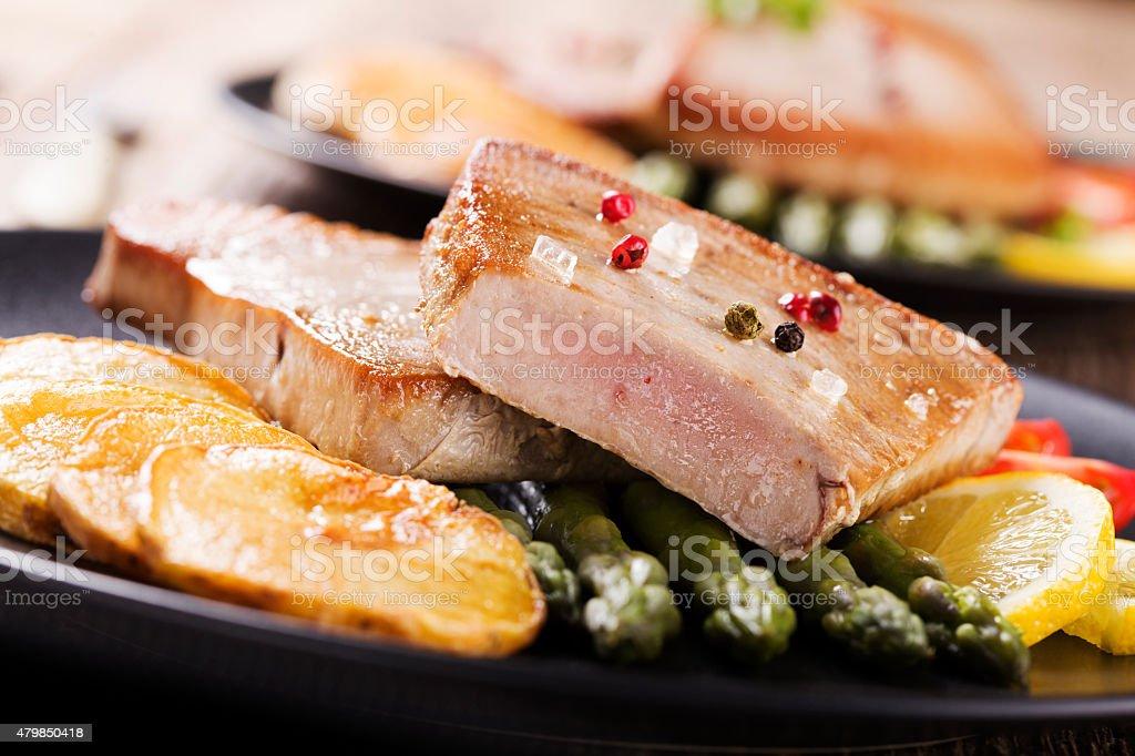 Grilled tuna steak served on asparagus with roasted zmieniakami stock photo