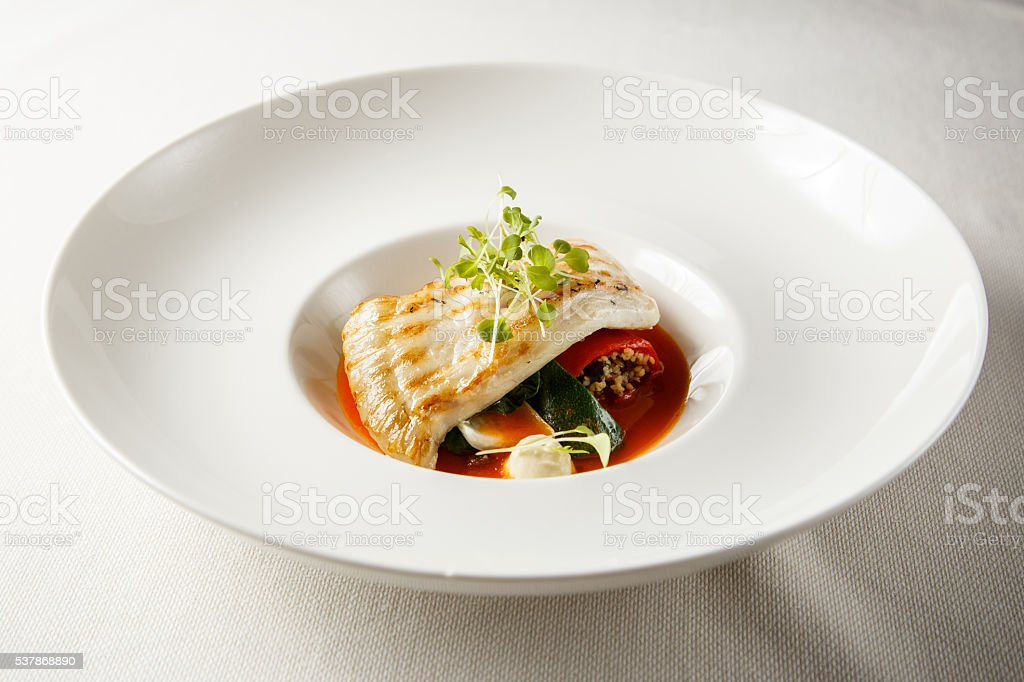 Grilled turbot, tabouli, sweet pepper sauce and summer vegetables. stock photo