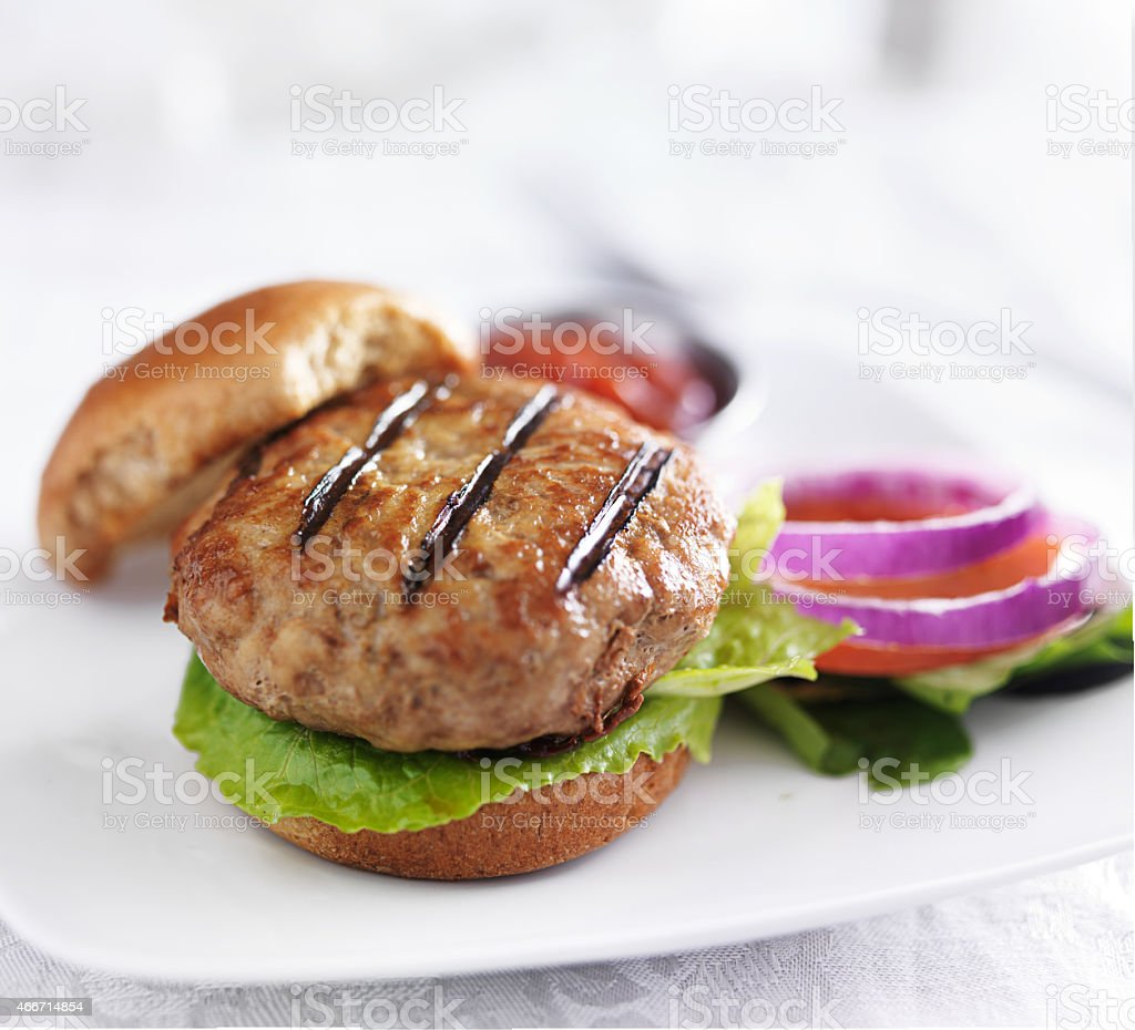 grilled turkey burger on white plate stock photo