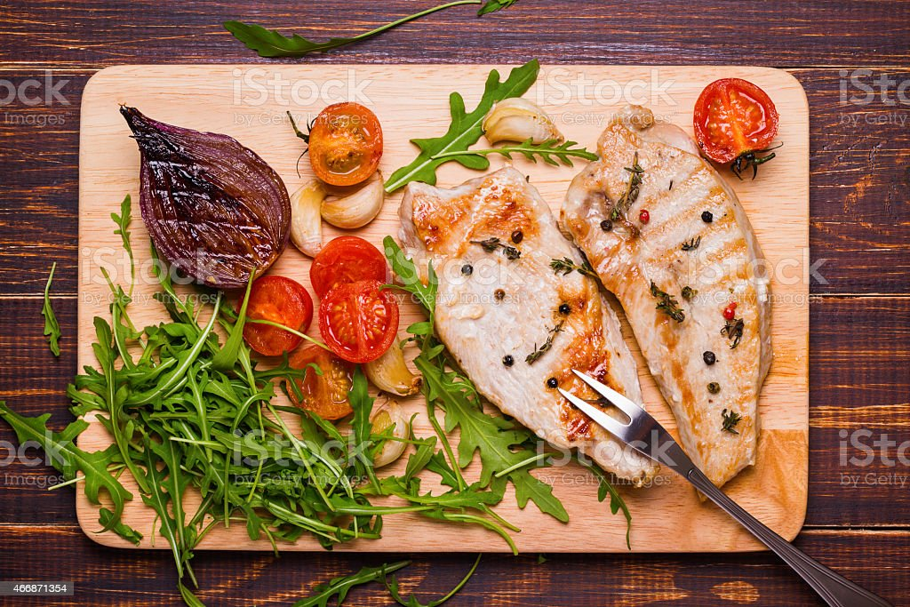 Grilled turkey steak on a cutting board stock photo
