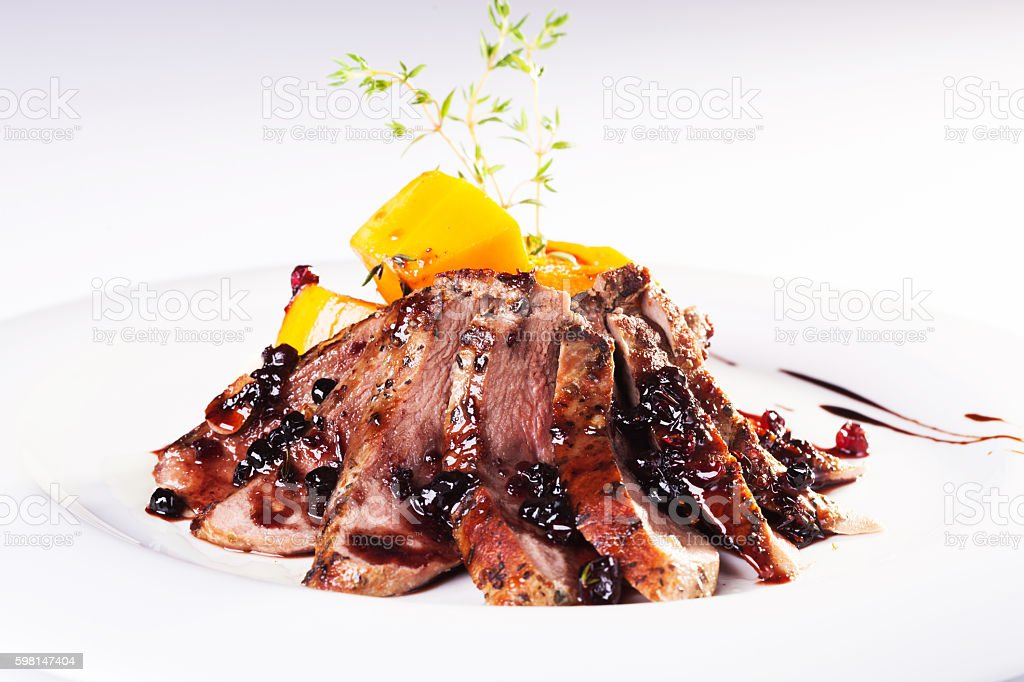 Grilled veal meat with red cranberry sauce stock photo