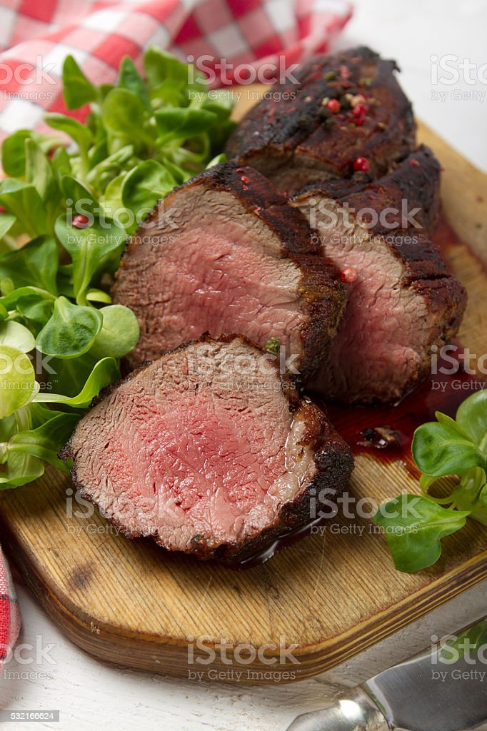 Grilled veal tenderloin with salad on a wooden board stock photo