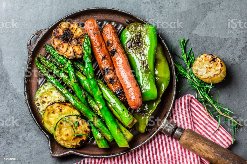 Grilled vegetables and sausages on cast iron grill pan. Gray slate background. stock photo