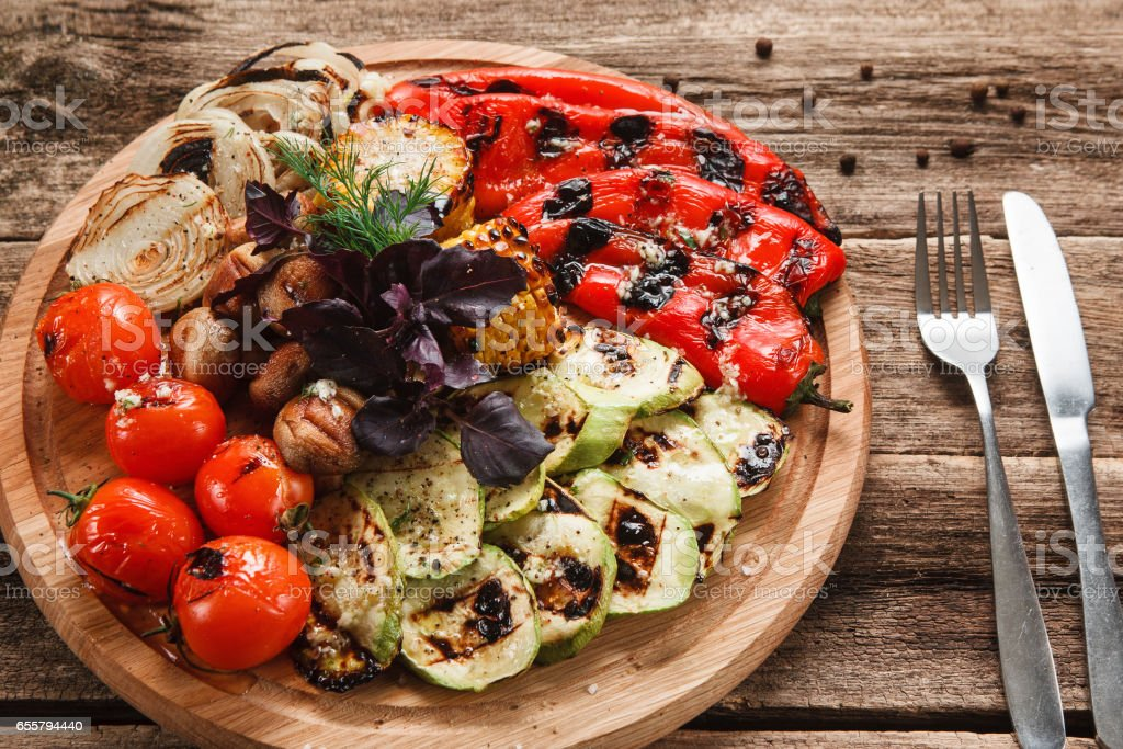 Grilled vegetables served on wood platter top view stock photo