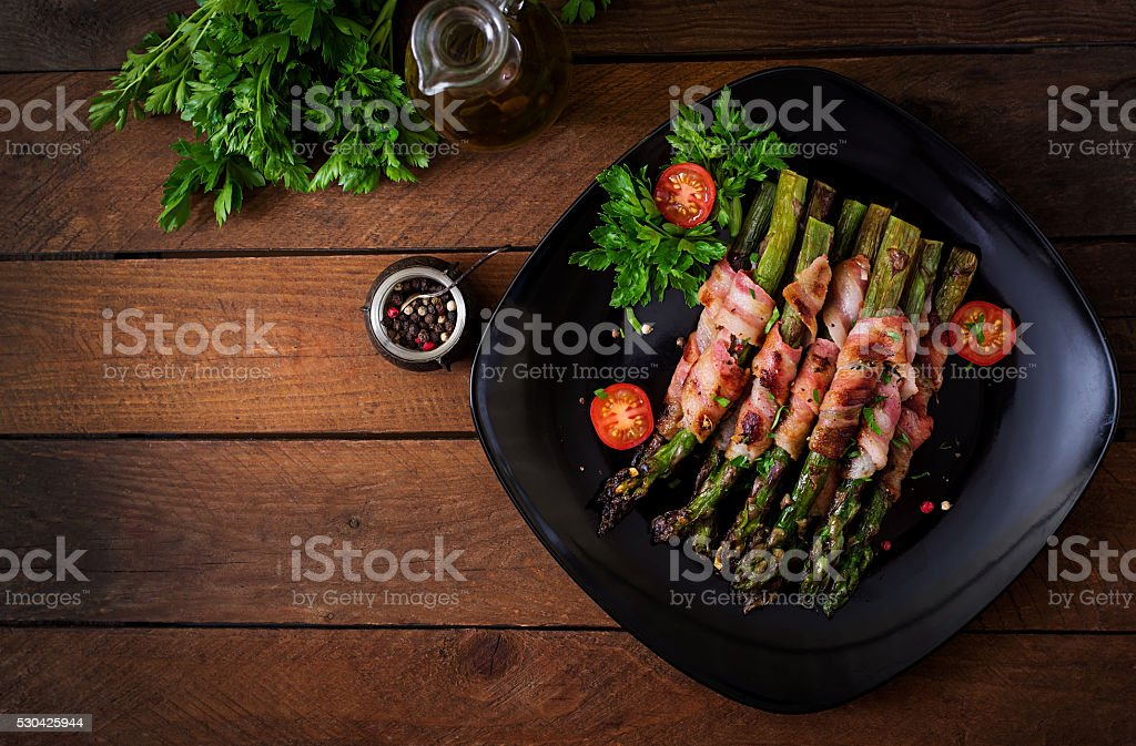 Grilled violet asparagus wrapped with bacon stock photo