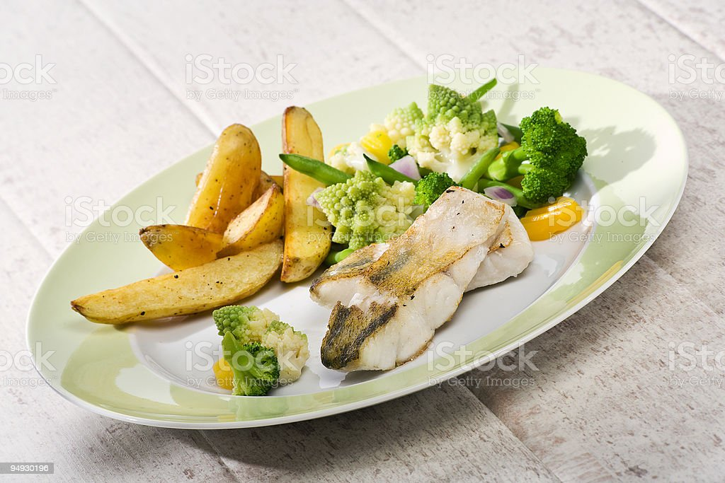grilled Zander dish with various vegetables and fried potatoes royalty-free stock photo