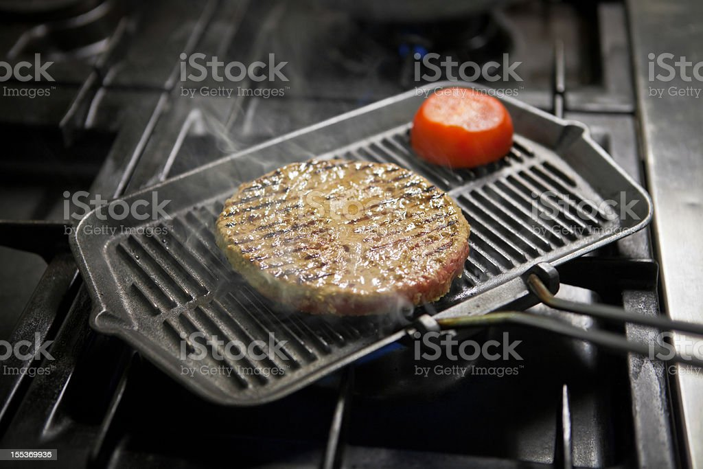 Grilling a hamburger with tomato royalty-free stock photo