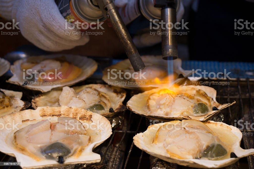 Grilling and burn oysters on flaming fire at Hokkaido morning stock photo
