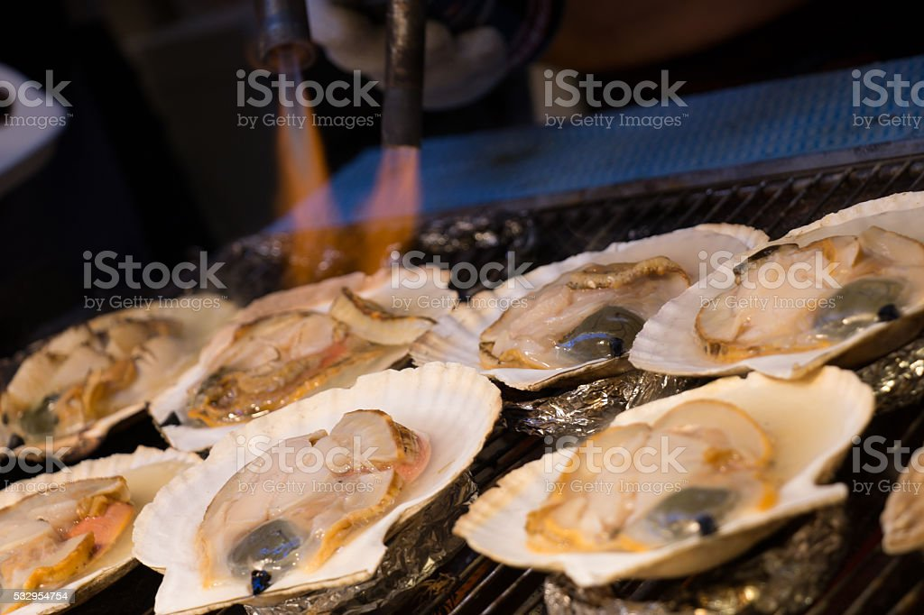 Grilling and burn oysters on flaming fire at Hokkaido stock photo