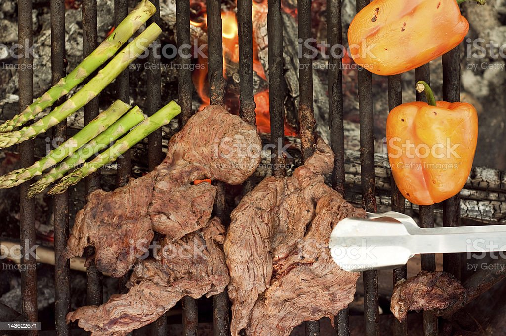 Grilling meat and veggies on an open fire stock photo