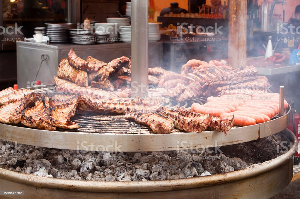 Grilling sausages and pork chop on large barbecue. stock photo