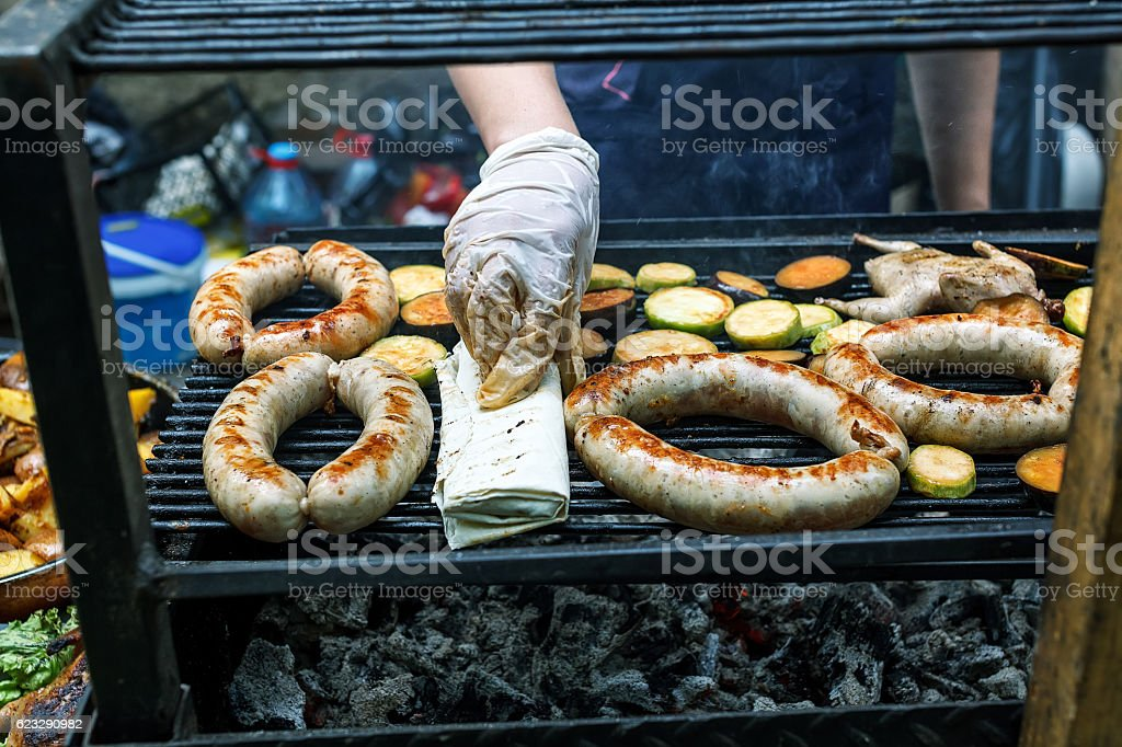 Grilling sausages and quail on the market showcase stock photo