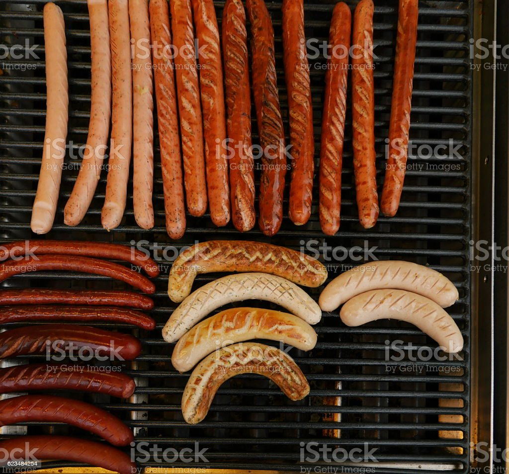 Grilling sausages on barbecue grill. stock photo