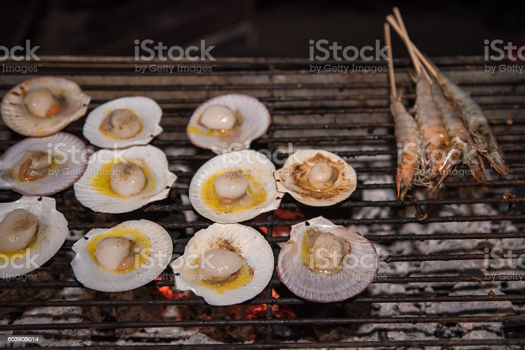 Grilling scallops with butter stock photo