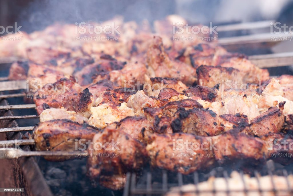 Grilling skewers or shashlik on barbecue grill. Selective focus stock photo
