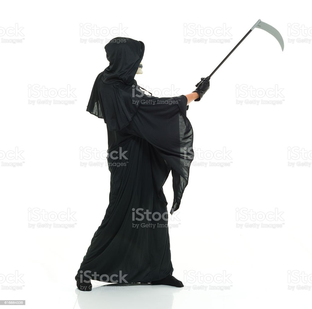 Grim reaper in action with scythe stock photo