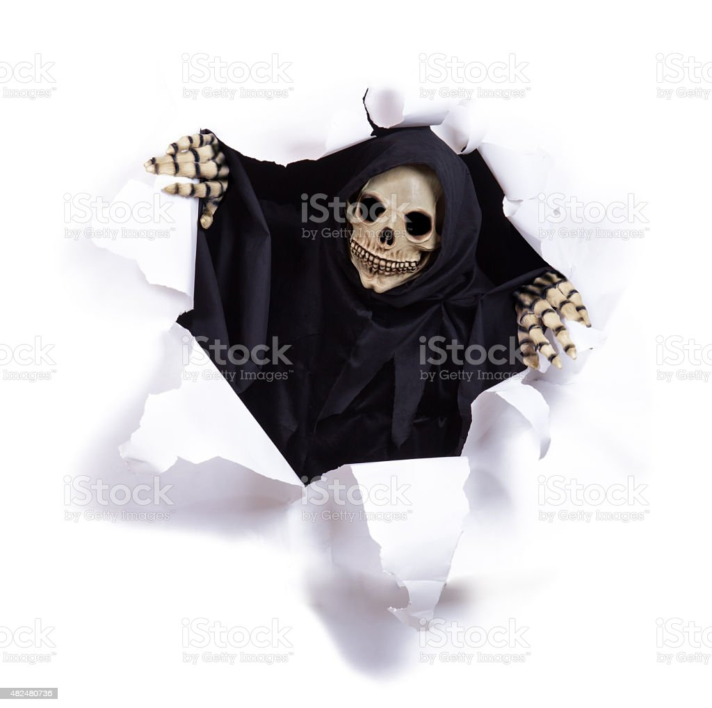Grim reaper looking through hole torn in white paper stock photo