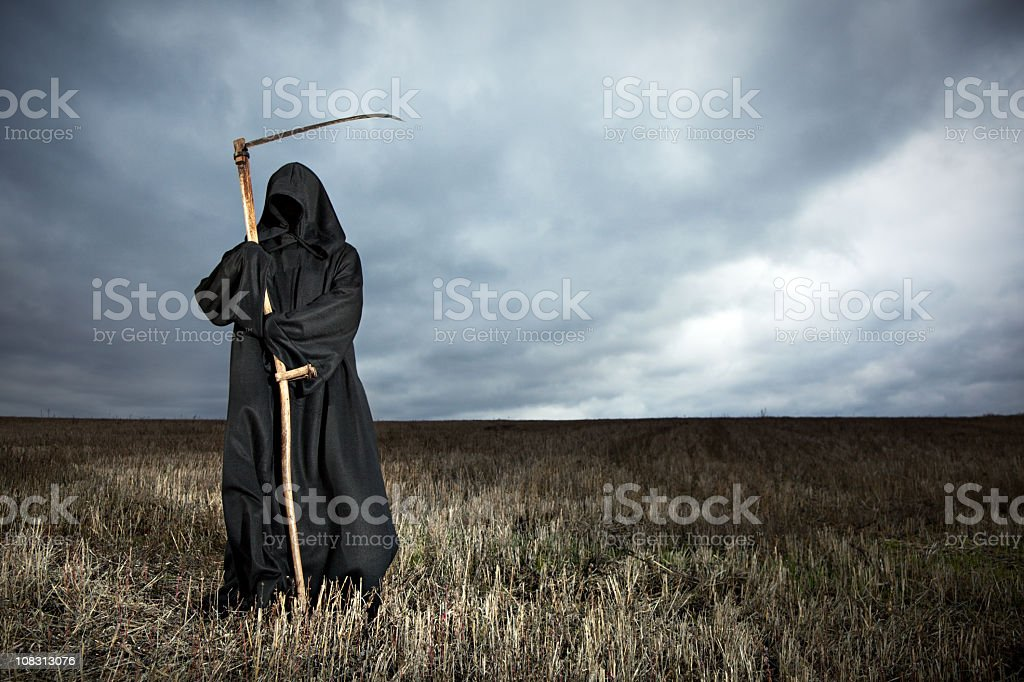 Grim Reaper standing in a field with stormy clouds overhead royalty-free stock photo