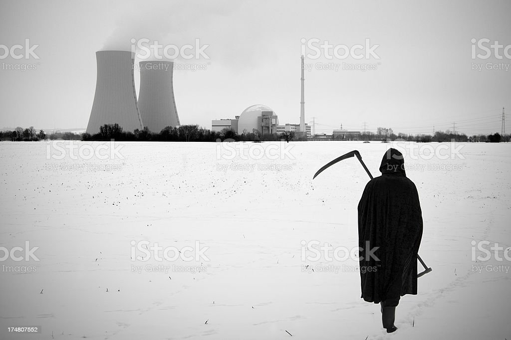 Grim reaper with scythe in front of nuclear power station royalty-free stock photo