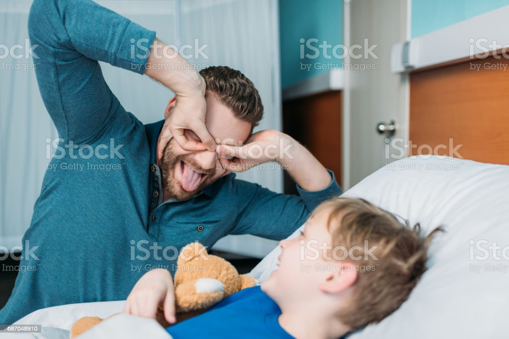 grimace dad and son having fun in hospital chamber stock photo