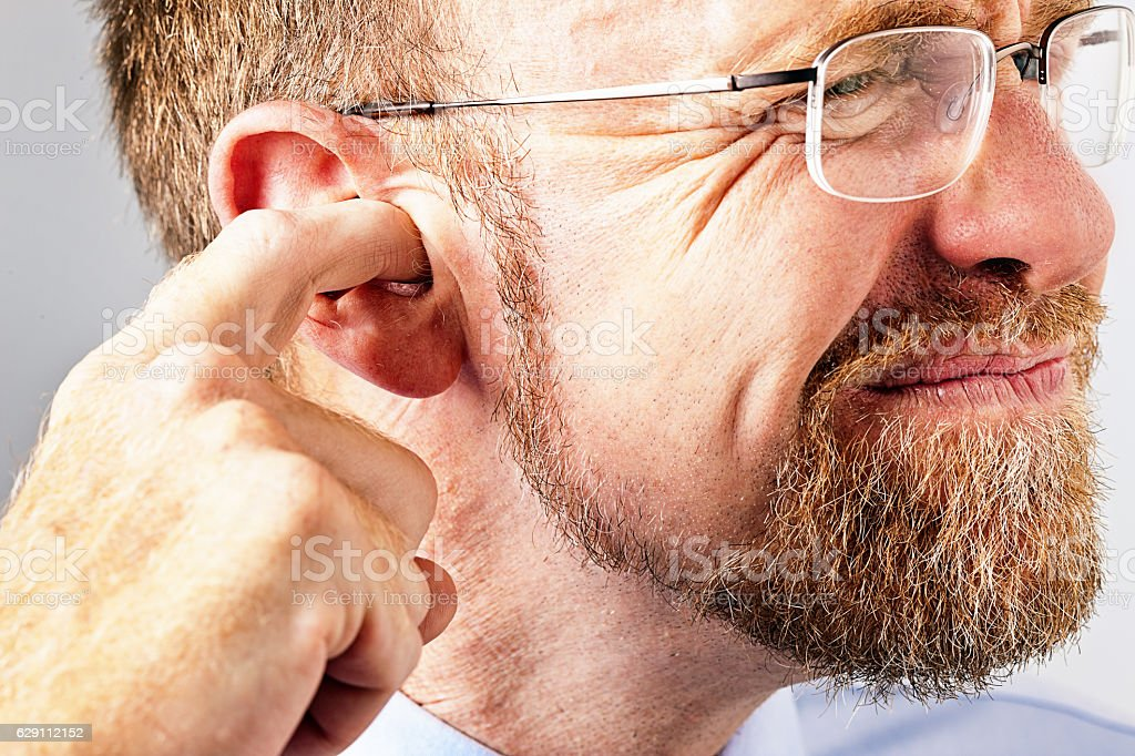 Grimacing middle-aged man digs in his ear stock photo
