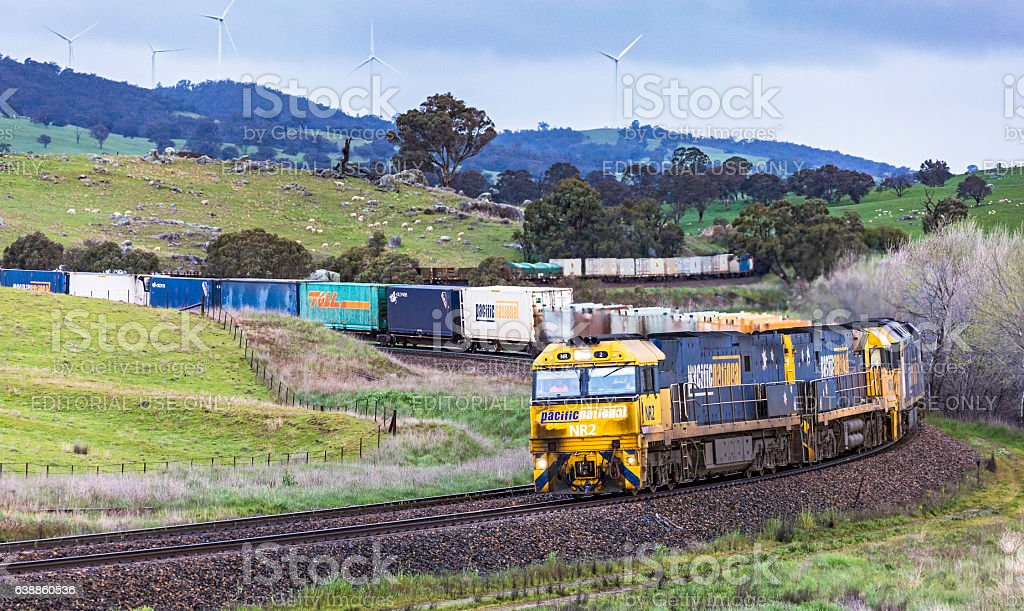 Grimy diesel train locomotives, contrast with clean wind power stock photo