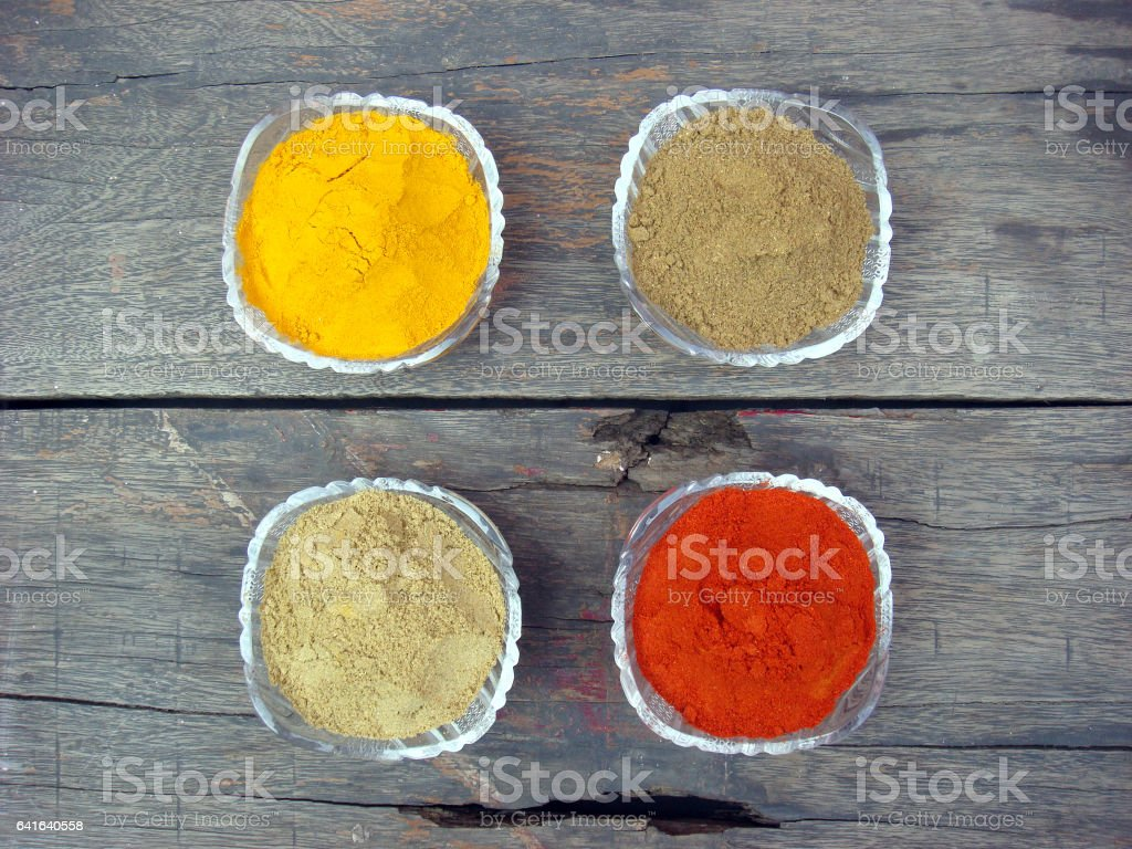 Grinded spices in glass bowl on rusted wooden stock photo