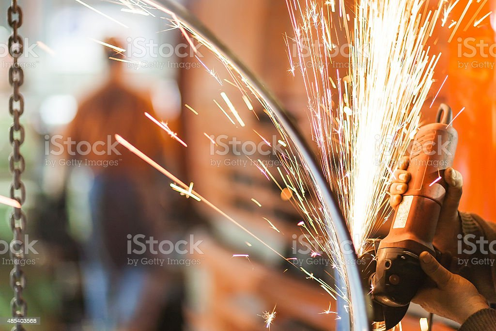 grinding big pipe with grinder: sparks stock photo