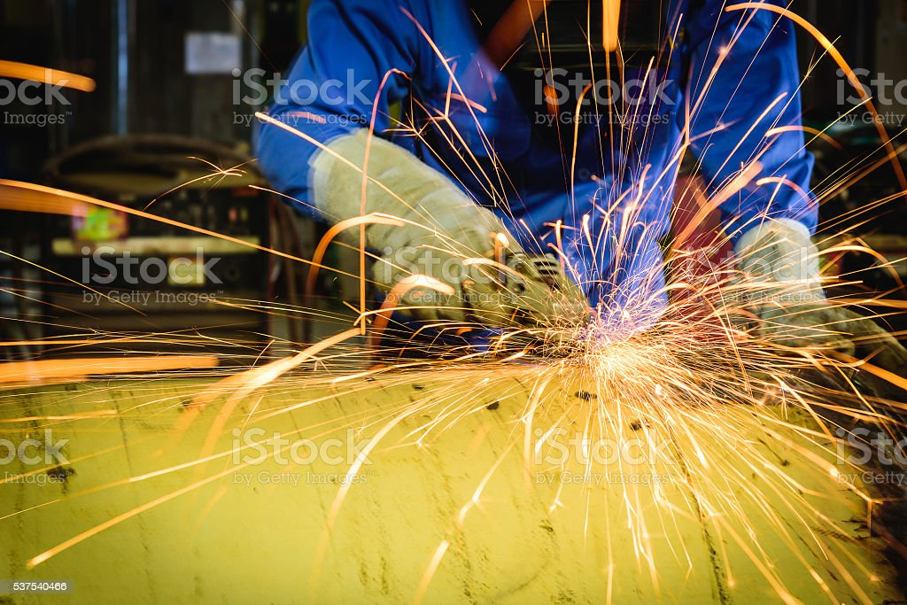 Grinding machine in action with bright sparks in construction factory. stock photo