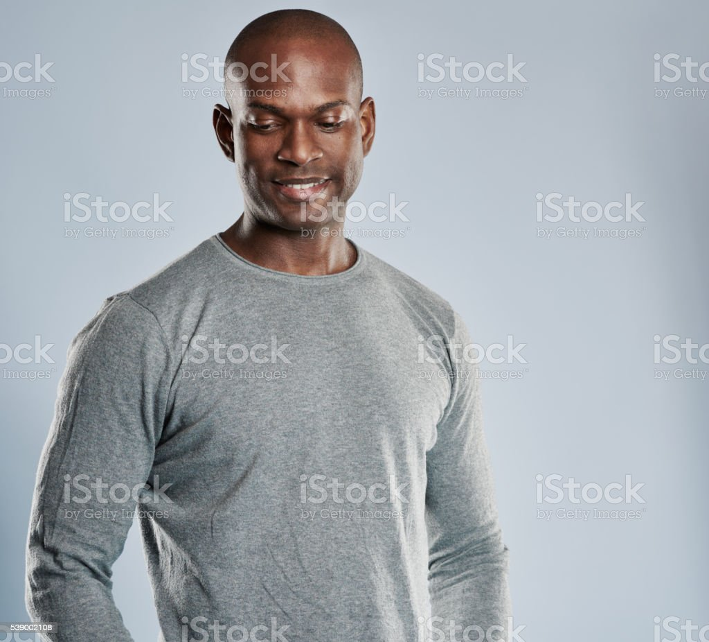 Grinning African man in gray shirt with copy space stock photo