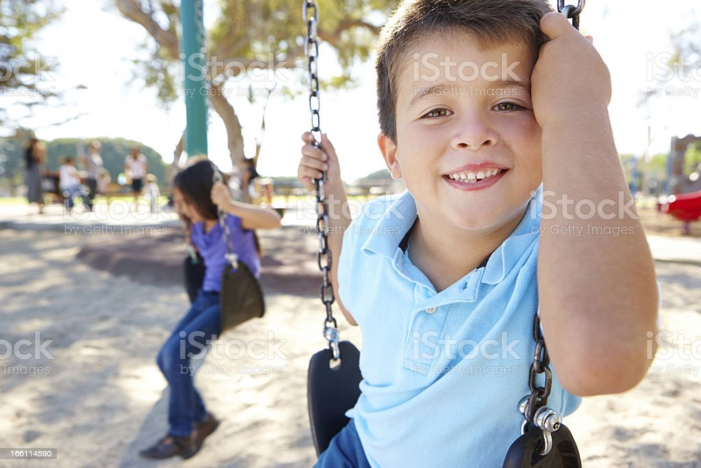 Grinning boy on a swing at a park with a girl in the back stock photo