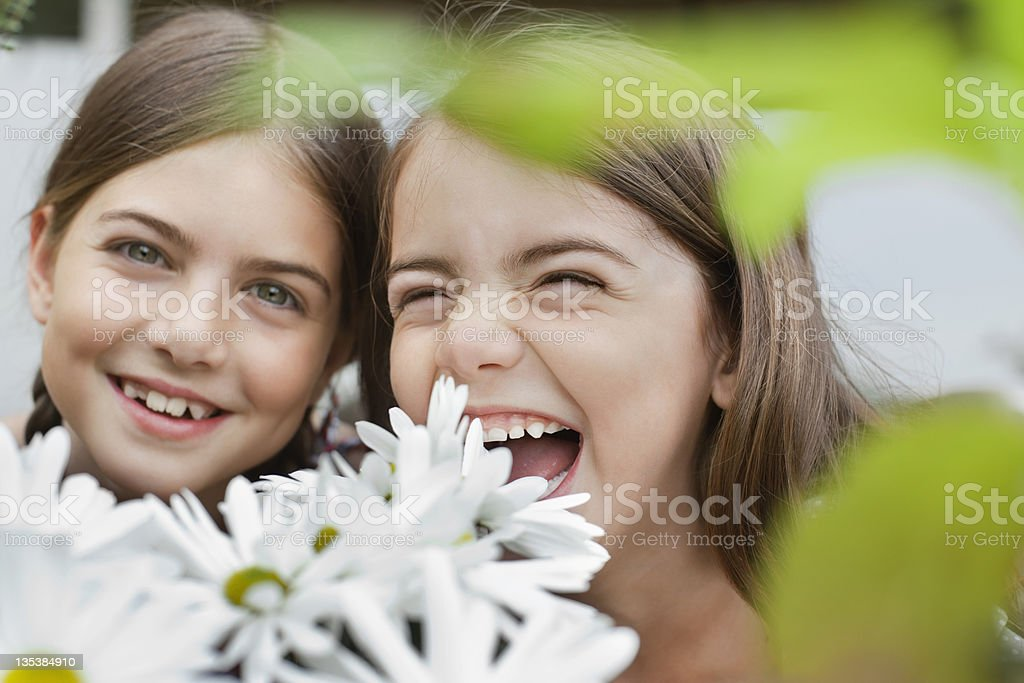 Grinning girls holding flowers royalty-free stock photo