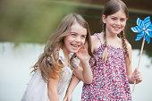 Grinning girls holding pinwheel