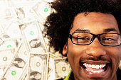 Grinning young man surrounded by cash cannot believe his luck