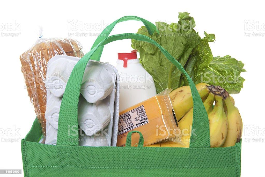 groceries in a green reusable shopping bag stock photo