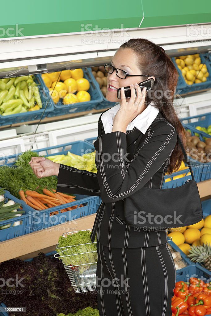 Grocery store - Businesswoman with mobile phone shopping in supermarket royalty-free stock photo