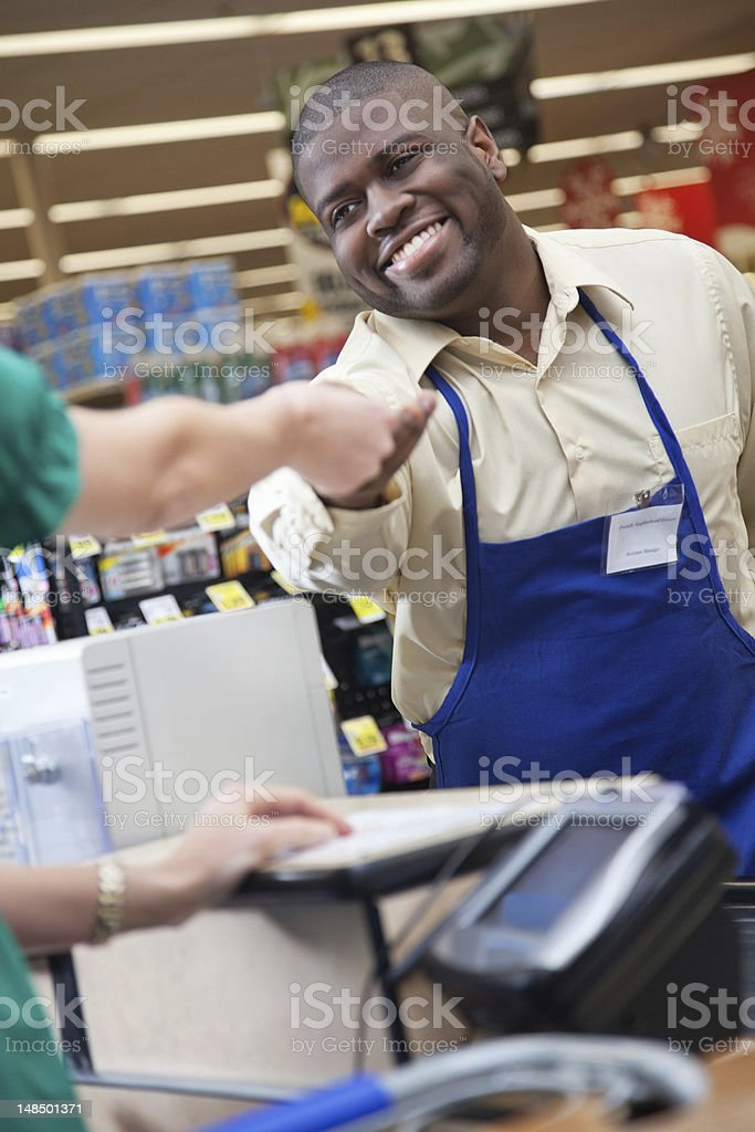 Grocery store clerk handing change back to customer at checkout royalty-free stock photo