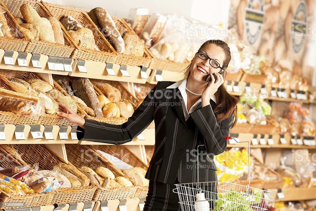 Grocery store: Young happy business woman shopping in supermarket royalty-free stock photo