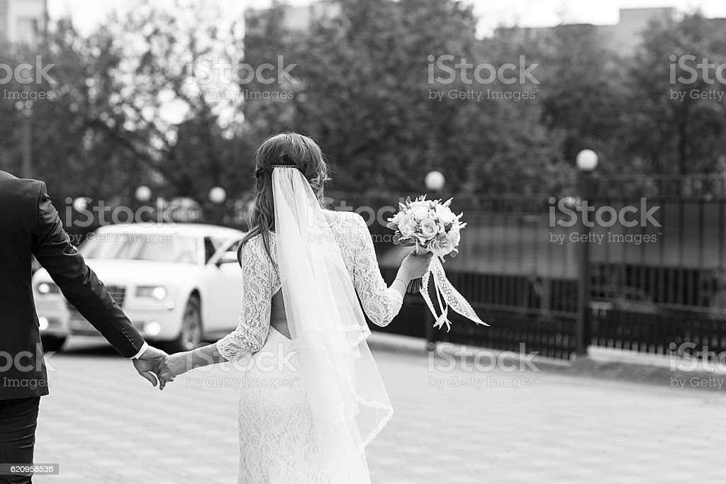 Groom and bride go to car stock photo