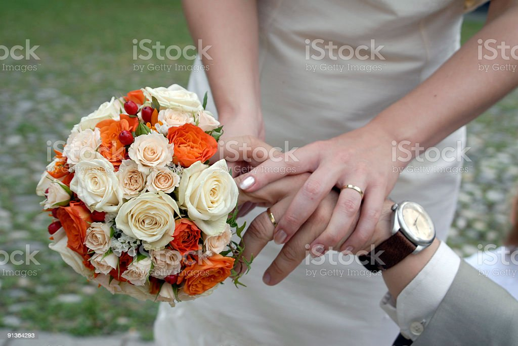 Groom and bride holding a wedding bouquet royalty-free stock photo
