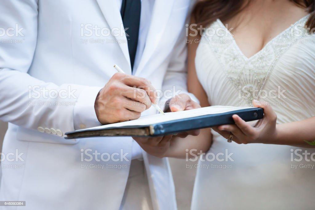 Groom and bride in white suit signing their marriage license stock photo