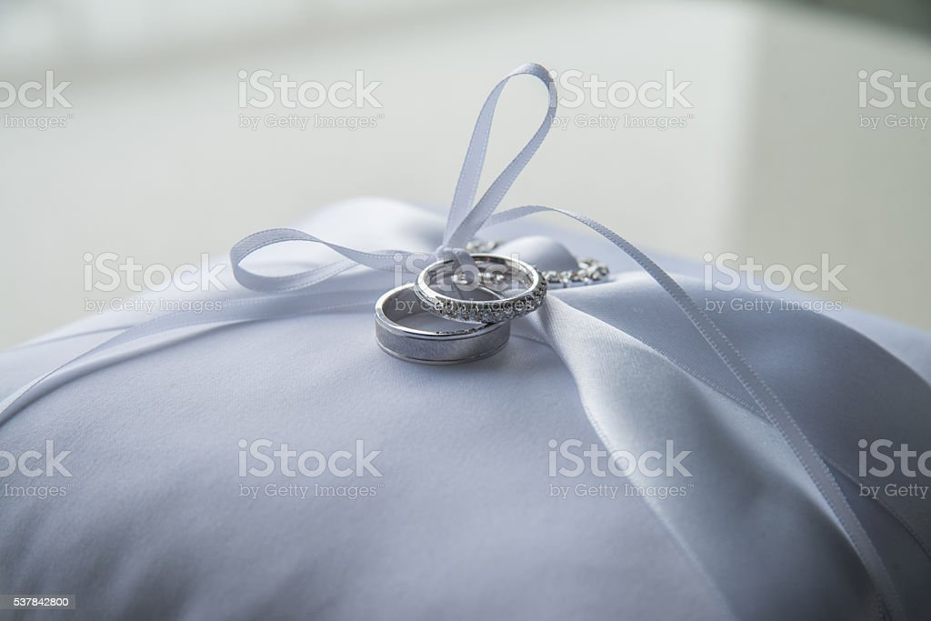 Groom and bride's wedding rings on a white ornamental pillow stock photo
