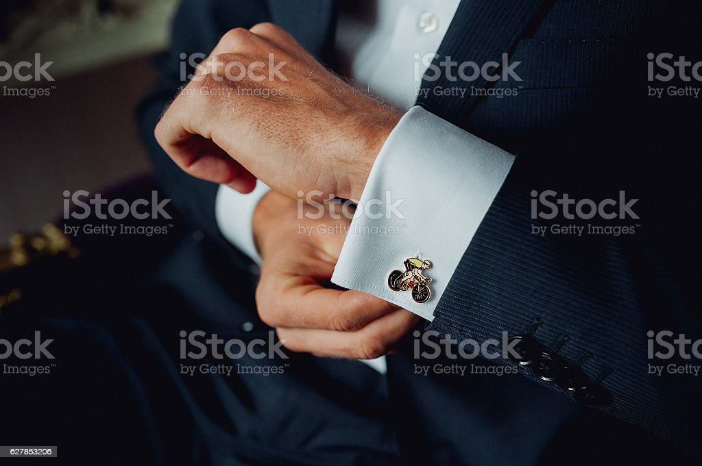 Groom buttoning a shirt on  white wedding stock photo